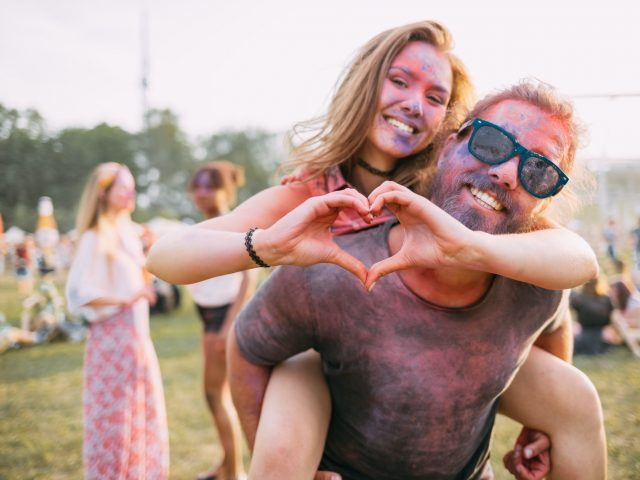 Beautiful couple covered in colorful powder having fun at summer holi festival