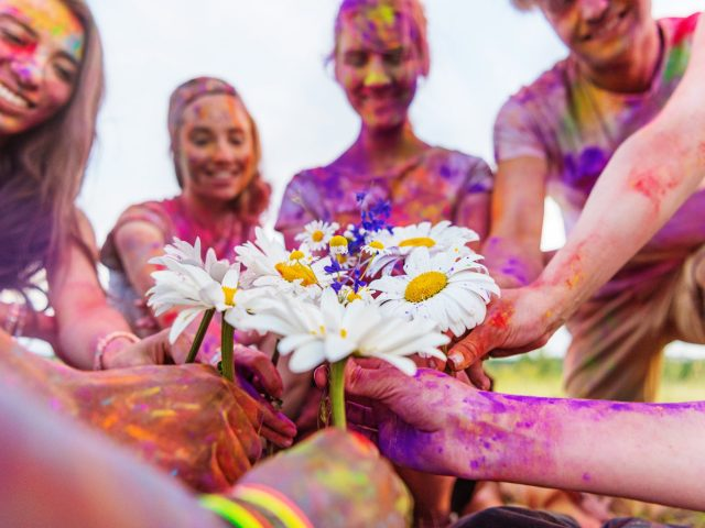 cropped shot of young friends holding chamomiles at holi festival